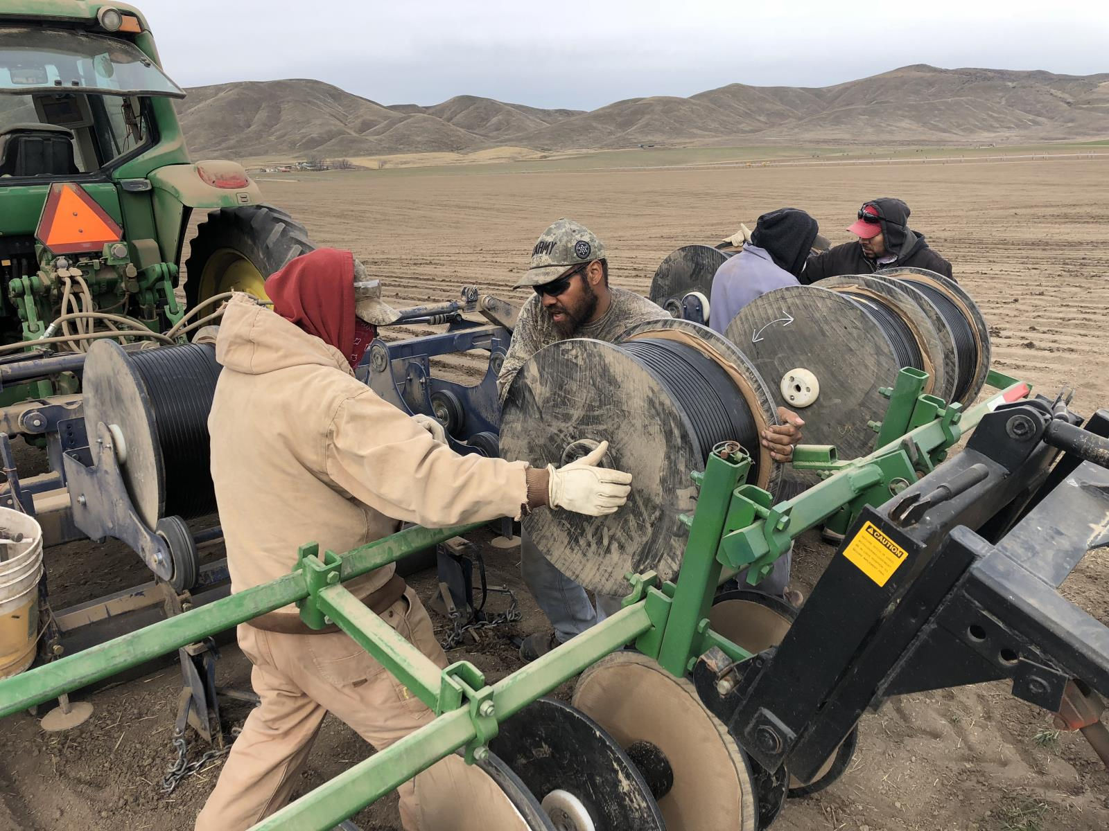 Farm workers earlier this spring prepare to lay drip irrigation tape in a field near Weiser will be planted to onions.
