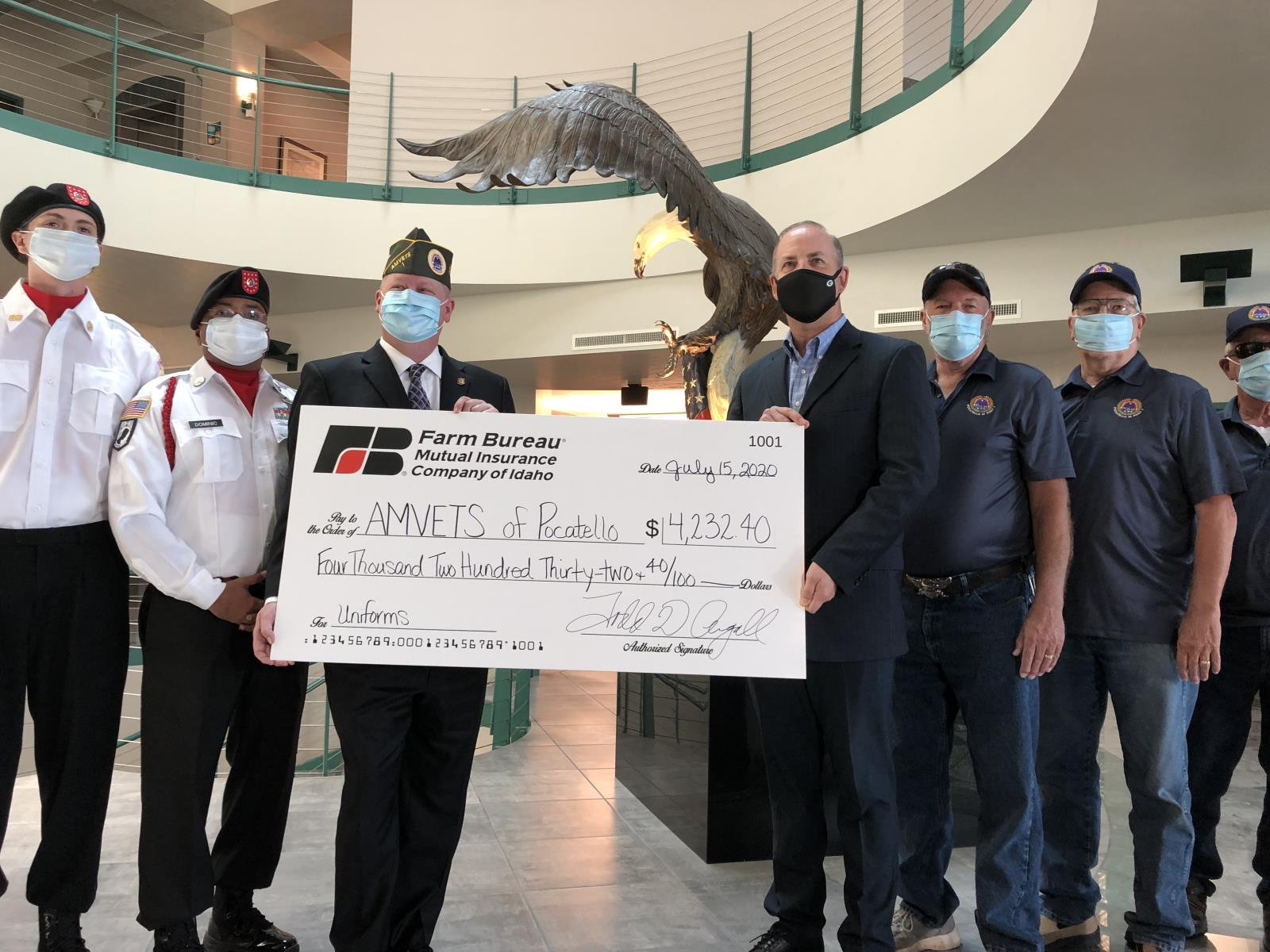 Farm Bureau Mutual Insurance Co. of Idaho CEO Todd Argall, center right, presents a check for $4,232 to AMVETS Pocatello Commander Lance Kolbet, center left, July 15. The money will be used to help the local AMVETS chapter start its honor guard.